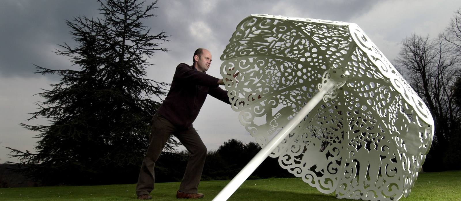 "Sculptor Bruce Williams arranges his steel canopy ""Parasol"" in the garden of the National Trust's Polesden Lacey"