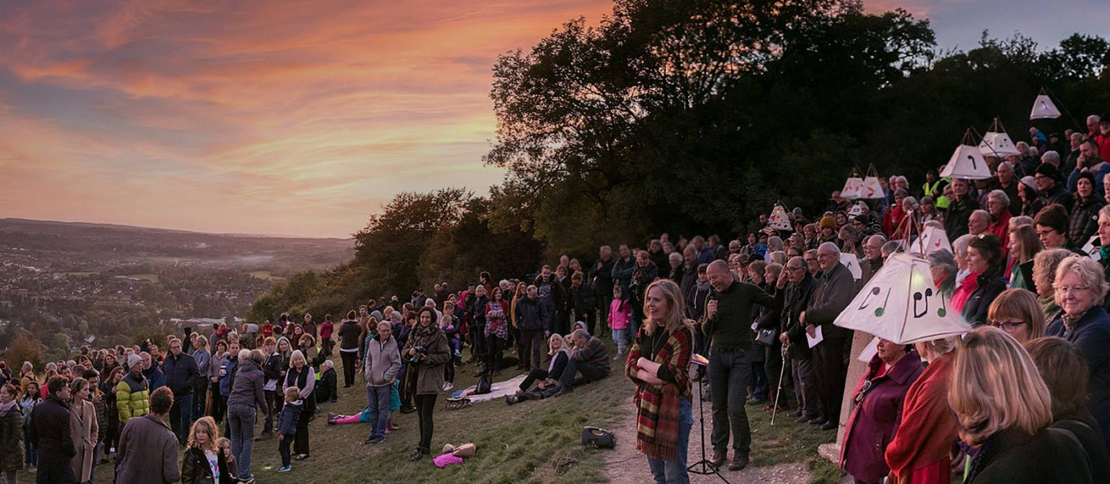Crowd standing on Box Hill at dusk